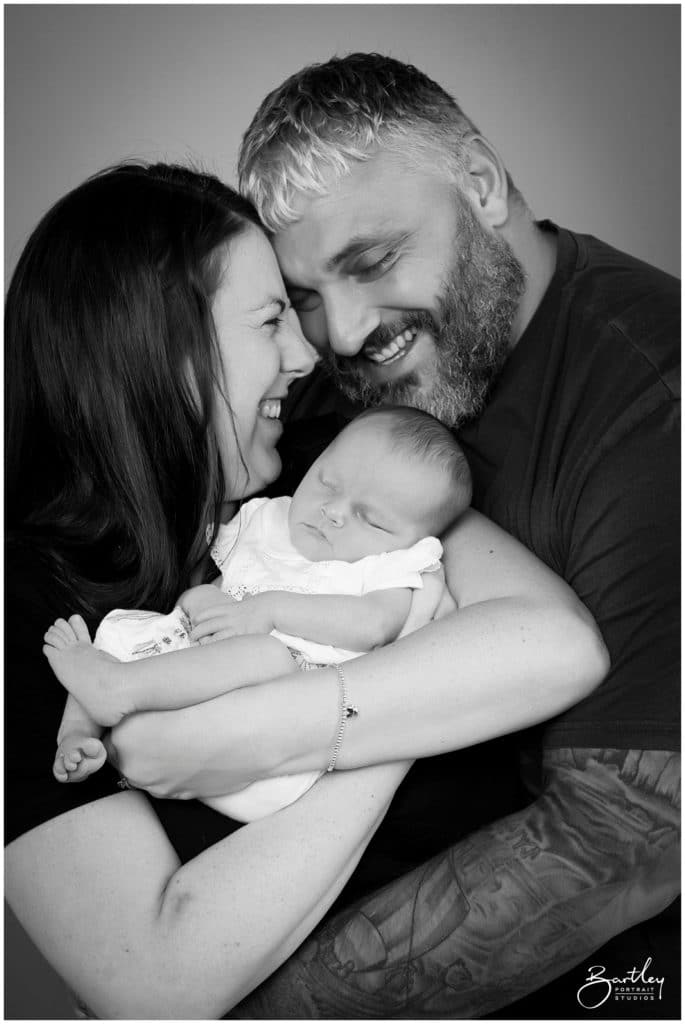 happy family mum and dad with newborn daughter