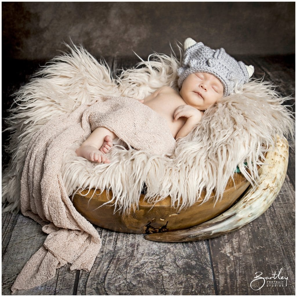 baby in viking knitted helmet asleep with drinking horn