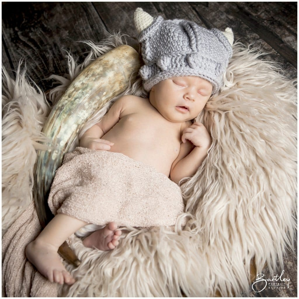 baby in viking knitted helmet asleep