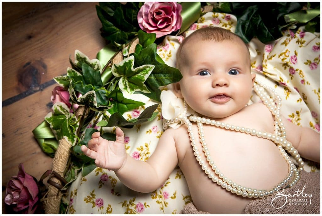 baby wearing pearls and surrounded by roses
