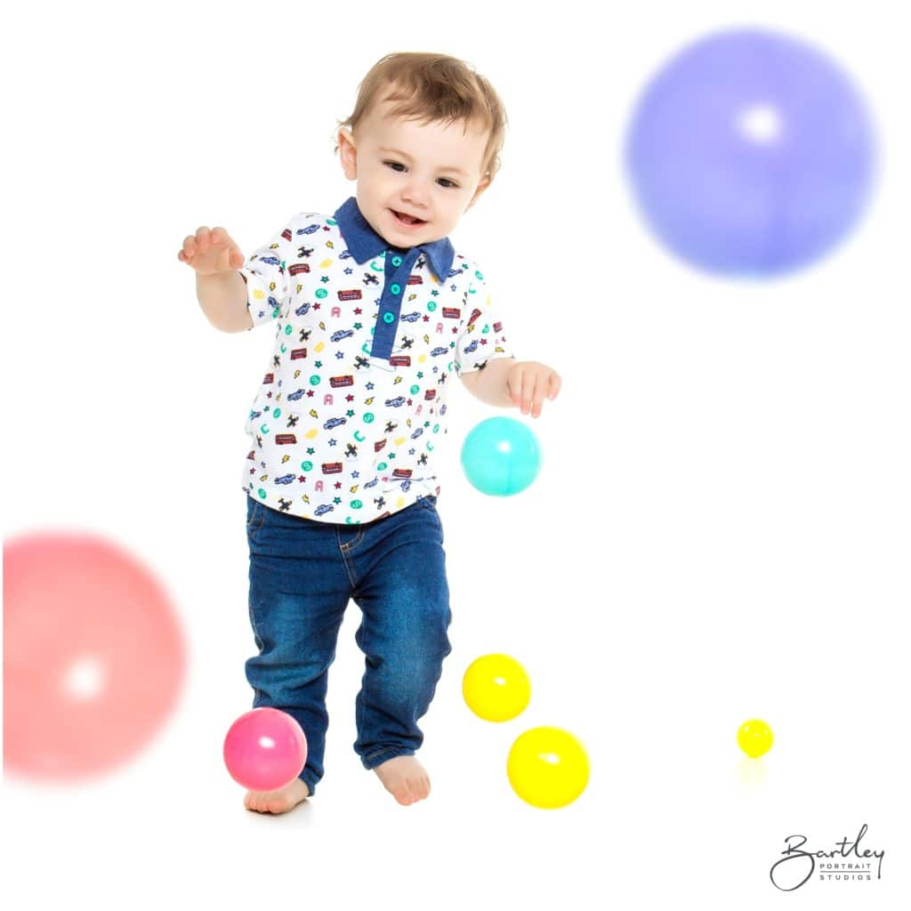 toddler playing in portrait studio with colourful balls