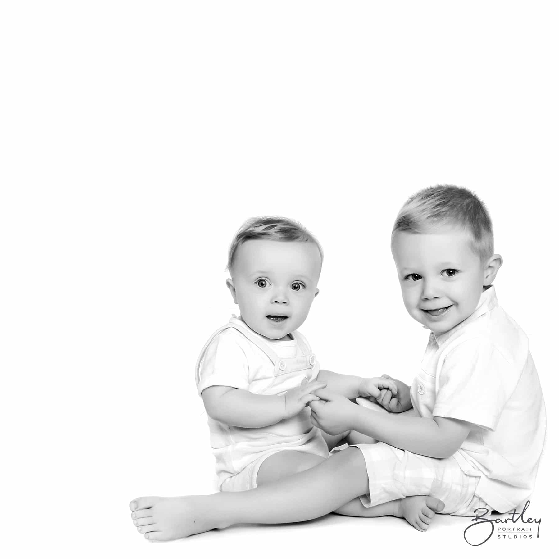 black and white studio shot of brothers holding hands