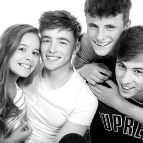 two sets of twins photoshoot smiling in the studio arms around each other