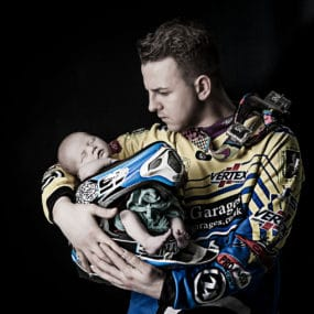 dad holding motorcross helmet with his precious newborn baby lay inside taken at Bartley Photography Studios in Warrington