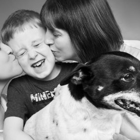 two mums kissing child with dog family portrait